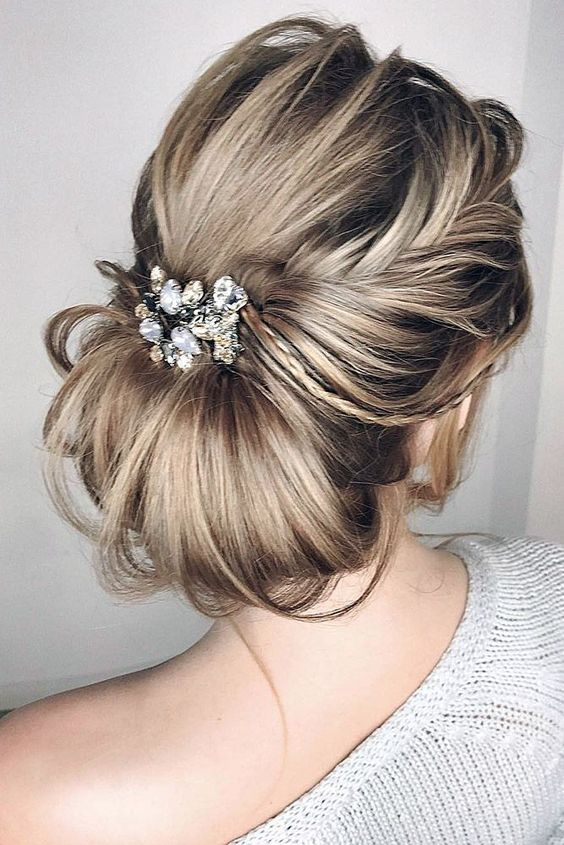 Picture Of a messy and textural low chignon hairstyle with a light .