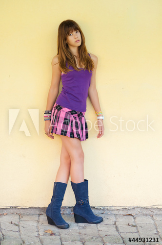 Beautiful teenage girl in short skirt and boots - Buy this stock .